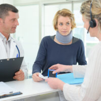 friendly female doctor with patient in office during reception filing insurance claim