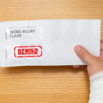 wrapped hand holding an envelope with a work injury claim application inside stamped with denied