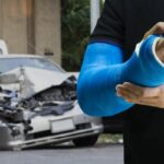 Man holding hand with blue bandage as arm injury with car accident concept.