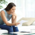 Worried woman reading lettter sitting at home