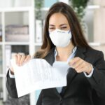 Executive wearing mask ripping contract at office